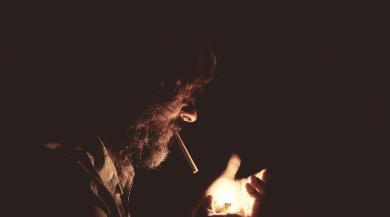 Мужчина закуривает сигарету