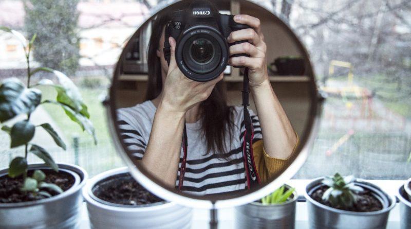 Девушка фотографирует себя через зеркало
