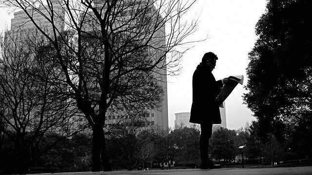 Мужчина в парке с газетой