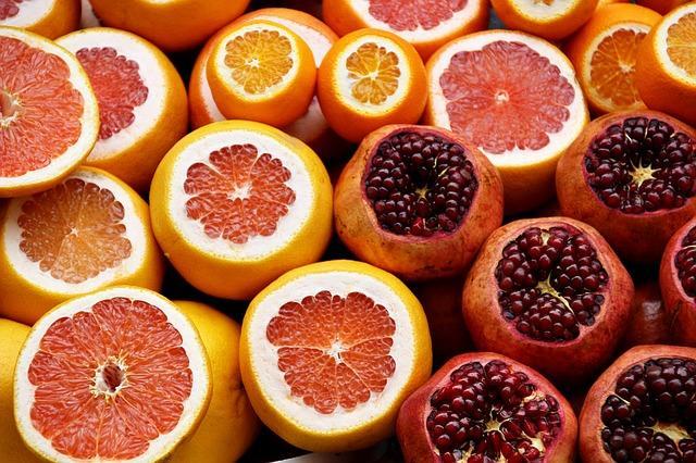 Сервировка граната и апельсинов на прилавке