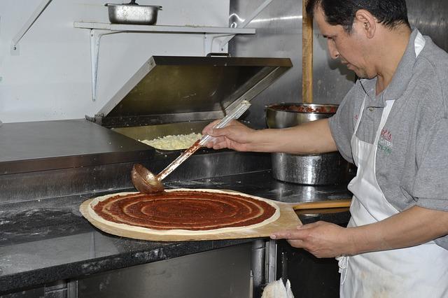 Итальянец готовит тесто для пиццы