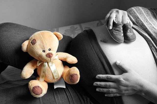 Беременная девушка с плюшевым мишкой