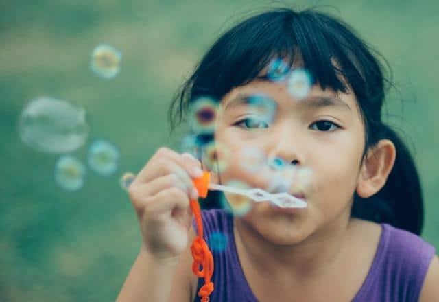 Девочка надувает мыльные пузыри