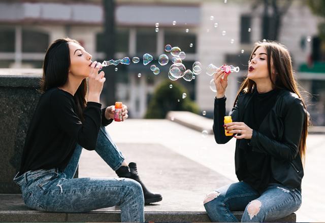 Девушки надувают мыльные пузыри