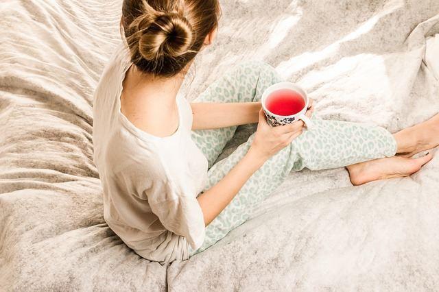 Женщина с чаем на кровати
